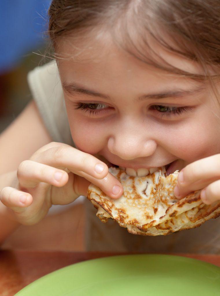 enfant qui mange une crêpe