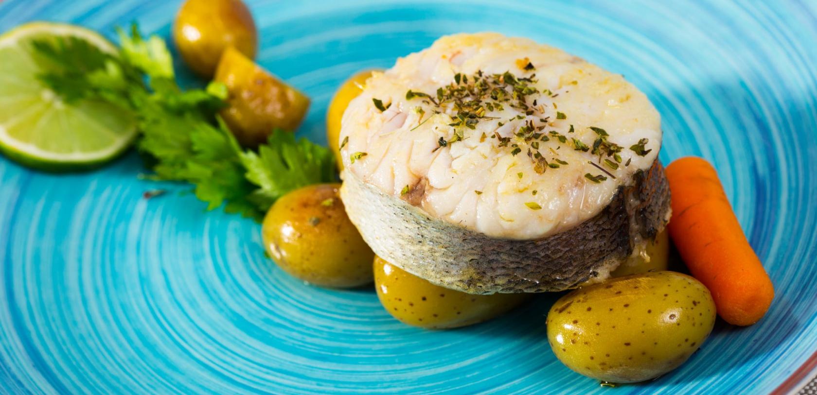 Tranche de merlu au court-bouillon aux aromates, pommes de terre et carottes.